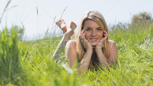 Pretty blonde in sundress lying on grass smiling at camera Stock photo © wavebreak_media