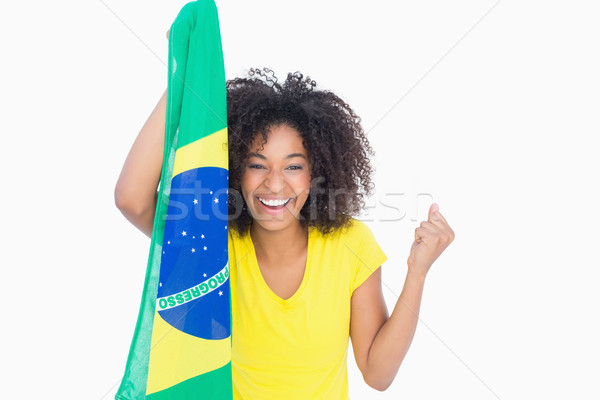 Pretty girl in yellow tshirt holding brazilian flag smiling at c Stock photo © wavebreak_media