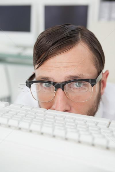 Nerdy businessman hiding behind keyboard Stock photo © wavebreak_media