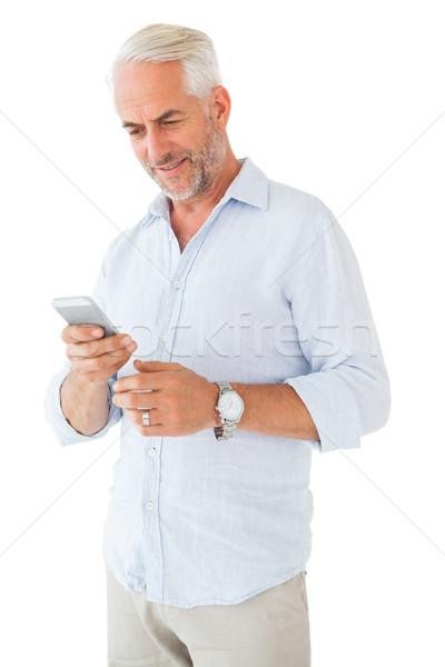 Smiling man sending a text message Stock photo © wavebreak_media