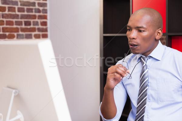 Serious businessman looking at computer monitor Stock photo © wavebreak_media