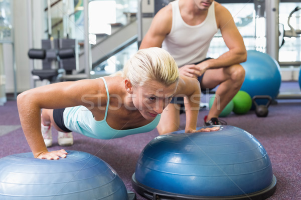 Male trainer assisting woman with push ups at gym Stock photo © wavebreak_media