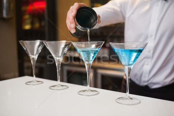Bartender pouring cocktail into glasses Stock photo © wavebreak_media