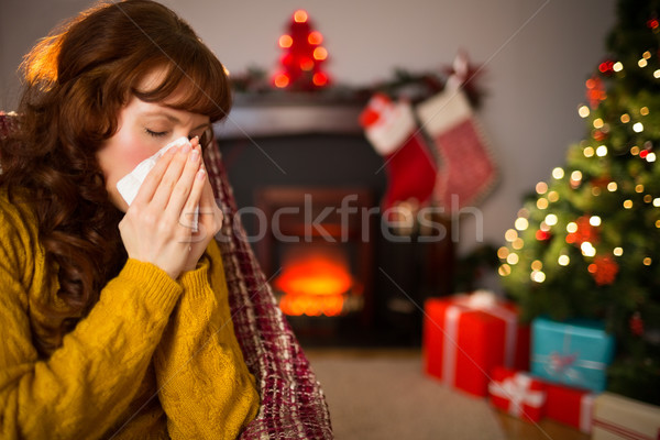Woman sitting on sofa and blowing her nose at christmas Stock photo © wavebreak_media