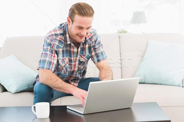 улыбаясь человека домой ноутбука сидят диван Сток-фото © wavebreak_media