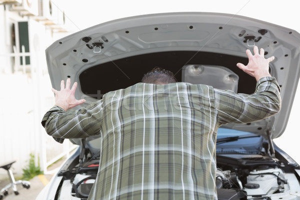 Angry man checking his car engine after breaking down Stock photo © wavebreak_media