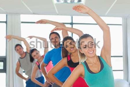 Happy friends practicing tree pose in fitness studio Stock photo © wavebreak_media