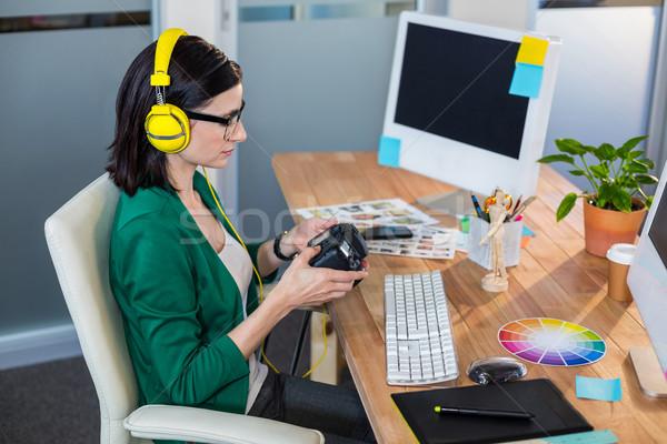 Brunette holding digital camera and listening music Stock photo © wavebreak_media