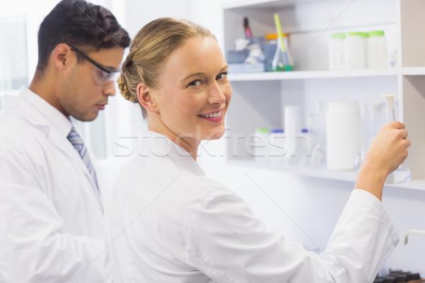 Uśmiechnięty naukowiec patrząc kamery zlewka Zdjęcia stock © wavebreak_media