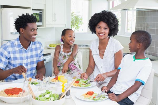 Happy family sitting down to dinner together Stock photo © wavebreak_media
