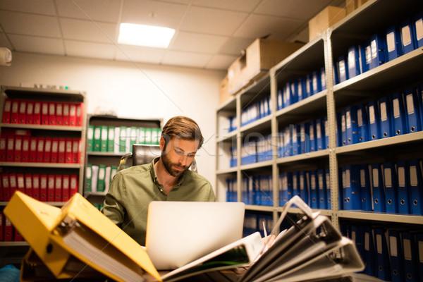 серьезный бизнесмен используя ноутбук файла месте Сток-фото © wavebreak_media
