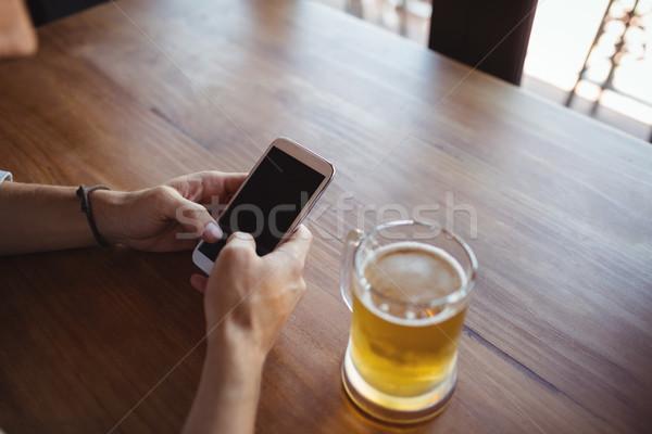 Man using mobile phone while having beer Stock photo © wavebreak_media
