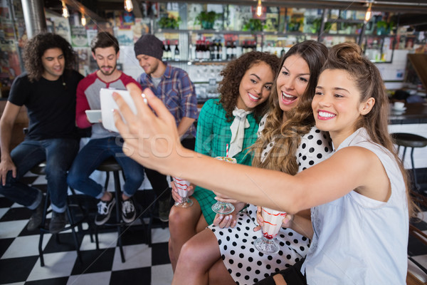 Cheerful female friends taking selfie in restaurant Stock photo © wavebreak_media