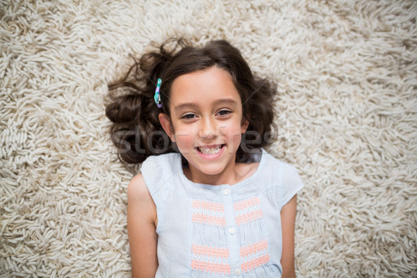 Portrait of smiling girl lying on rug in living room Stock photo © wavebreak_media