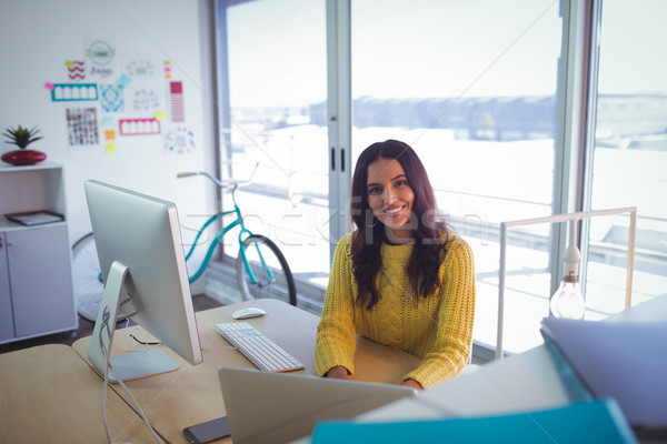 Smiling businesswoman sitting in creative office Stock photo © wavebreak_media