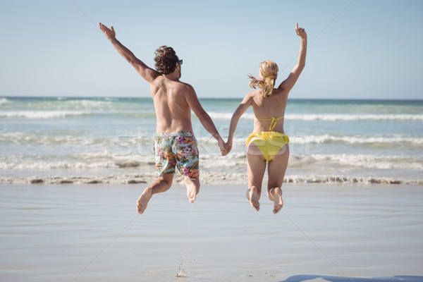 Rear view of couple holding hands while jumping at beach Stock photo © wavebreak_media
