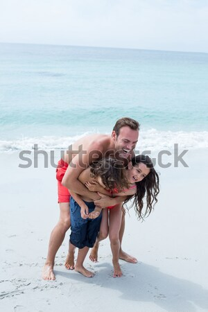 Young woman carving heart shape in sand while sitting with boyfriend at beach Stock photo © wavebreak_media