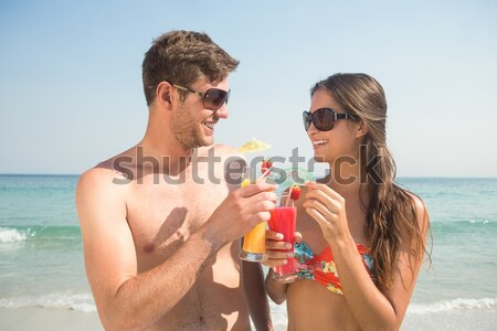 Smiling young woman applying sunscream on man nose at beach Stock photo © wavebreak_media