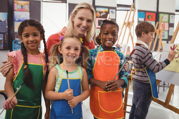 Teacher and schoolkid standing together in drawing class Stock photo © wavebreak_media