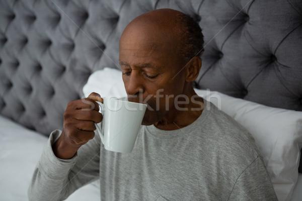 Senior man drinking coffee while sitting on bed Stock photo © wavebreak_media
