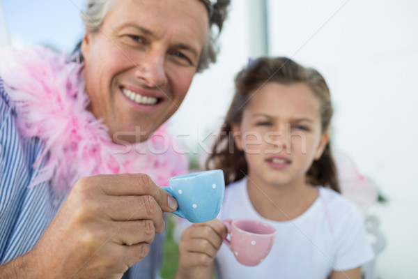 Smiling father and daughter in fairy costume having a tea party Stock photo © wavebreak_media