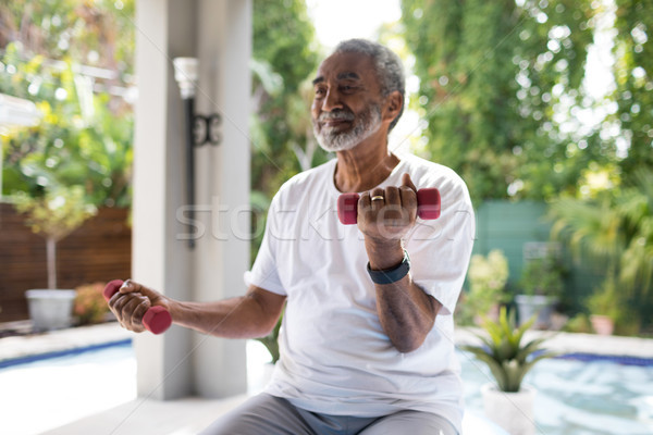 Senior man lifting dumbbell while exercising Stock photo © wavebreak_media