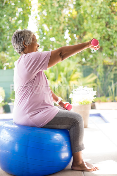 Side view of senior woman lifting dumbbells while exercising Stock photo © wavebreak_media