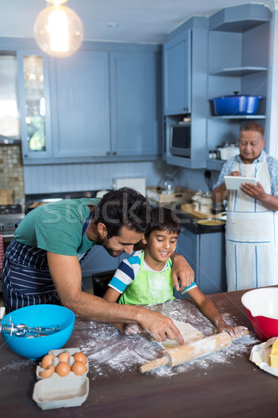 Father assisting son for rolling dough Stock photo © wavebreak_media