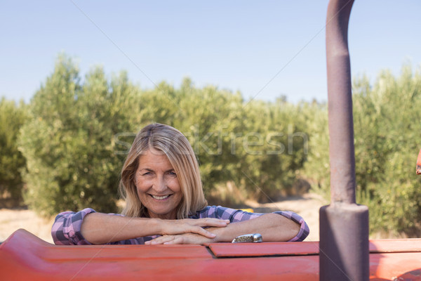 Portrait of happy woman leaning on tractor in olive farm Stock photo © wavebreak_media