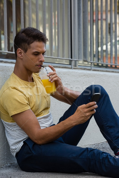 Young man having drink while using mobile phone Stock photo © wavebreak_media