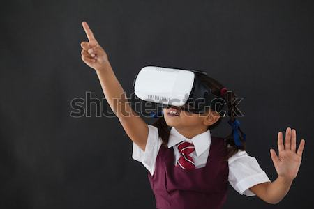 Schoolgirl using virtual reality headset against blackboard Stock photo © wavebreak_media