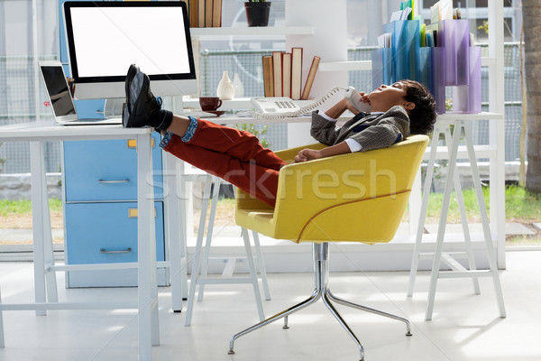 Biznesmen mówić telefonu posiedzenia krzesło stóp Zdjęcia stock © wavebreak_media