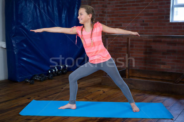 Happy teenage girl performing warrior pose Stock photo © wavebreak_media