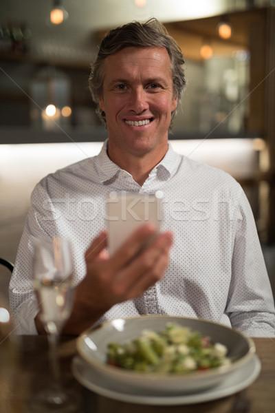 Gelukkig man mobiele telefoon dining restaurant portret Stockfoto © wavebreak_media