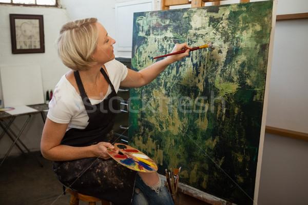 Attentive woman painting on canvas Stock photo © wavebreak_media