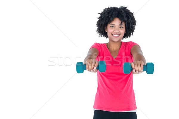 Portrait of happy young woman exercising with dumbbells Stock photo © wavebreak_media