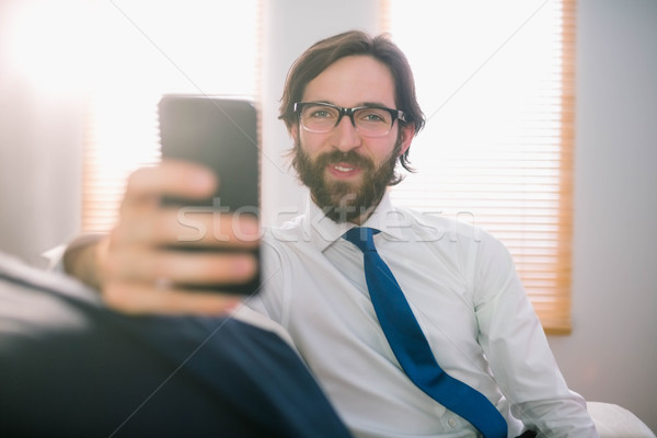 Businessman sending a text on the couch Stock photo © wavebreak_media