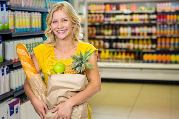 Smiling woman standing in aisle with grocery bag Stock photo © wavebreak_media