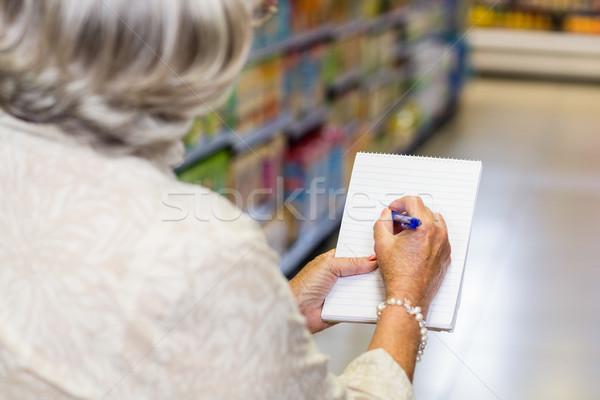 Senior woman checking list at the supermarket Stock photo © wavebreak_media