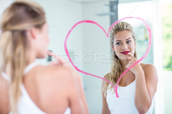 Woman with lipstick looking in the mirror Stock photo © wavebreak_media