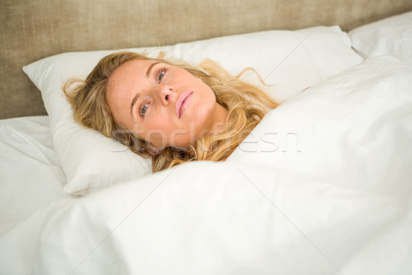 Pretty woman looking tired and lying in bed Stock photo © wavebreak_media