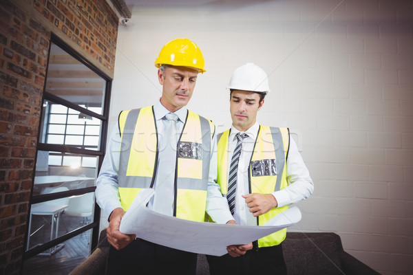 Architects discussing while holding blueprint  Stock photo © wavebreak_media