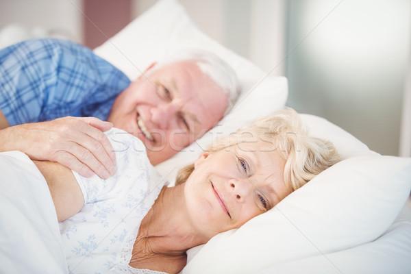 Portrait of smiling senior woman relaxing besides man on bed Stock photo © wavebreak_media