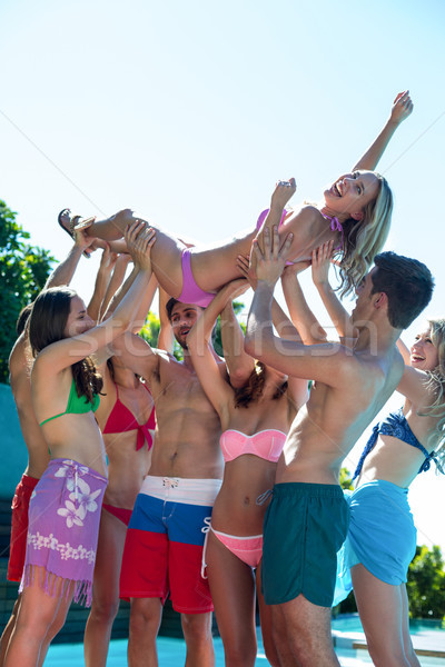 Group of friends lifting a woman near the pool Stock photo © wavebreak_media