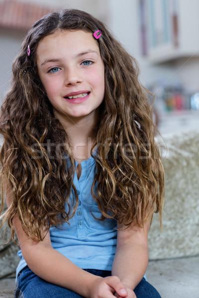 Portrait of girl sitting on sofa Stock photo © wavebreak_media