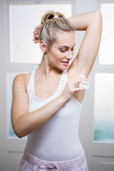Young woman applying powder on her underarms Stock photo © wavebreak_media