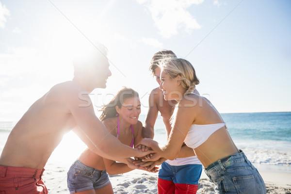 Barátok kezek együtt tengerpart nő víz Stock fotó © wavebreak_media
