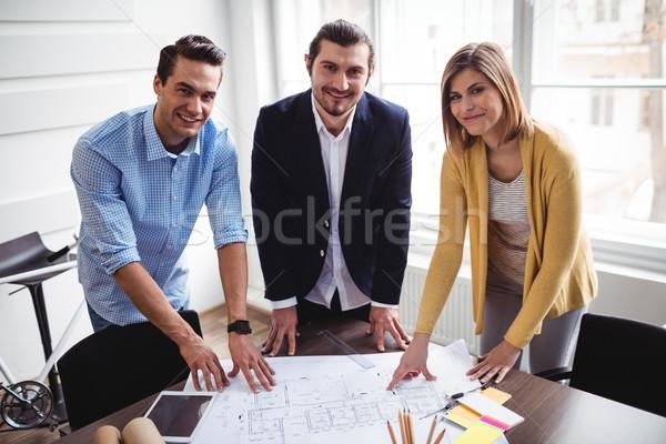 Smiling business people with blueprint Stock photo © wavebreak_media