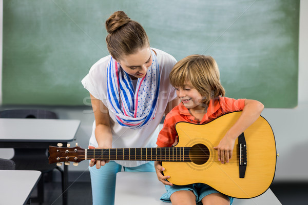 Teacher assisting boy to play guitar Stock photo © wavebreak_media