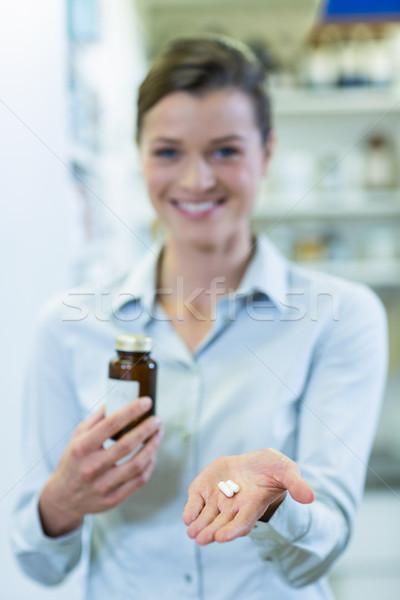 Pharmacist showing a medicine bottle and pills in pharmacy Stock photo © wavebreak_media